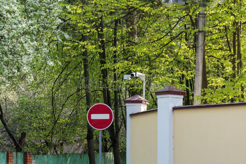 No entry Road sign and the security camera on the background of green trees stock image