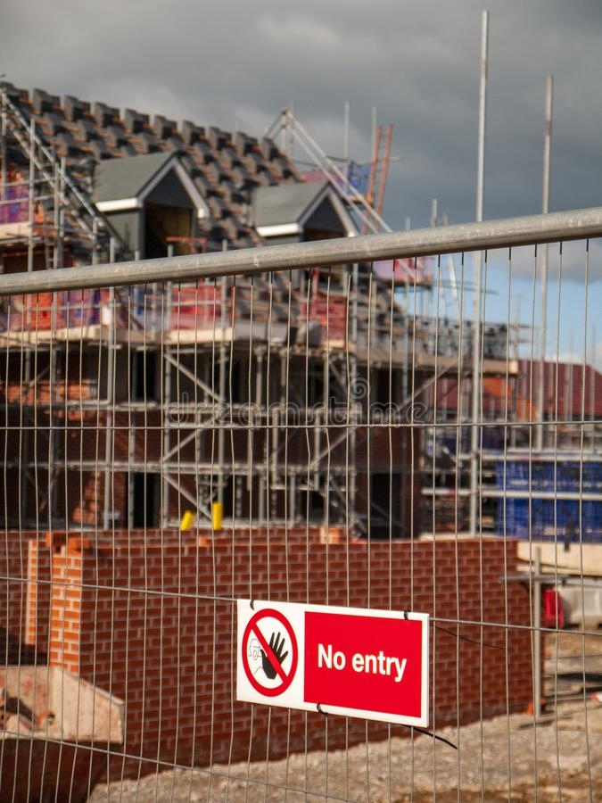 No entry warning sign on building site fence UK. No entry security warning sign on protected building site with new homes near completion in Cheshire England royalty free stock photos