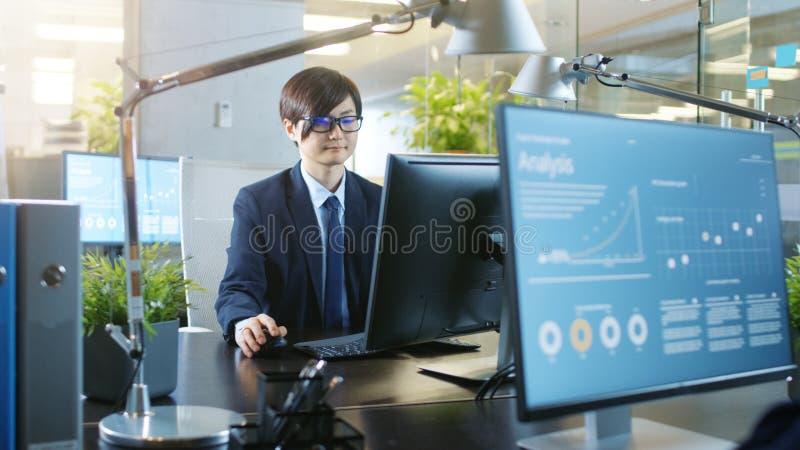 No escritório o homem de negócios asiático do leste de sorriso trabalha em um Desktop fotografia de stock royalty free