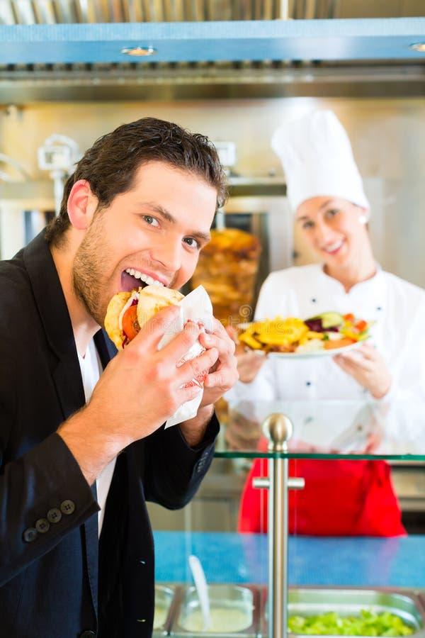 No espeto - cliente e Doner quente com ingredientes frescos foto de stock royalty free