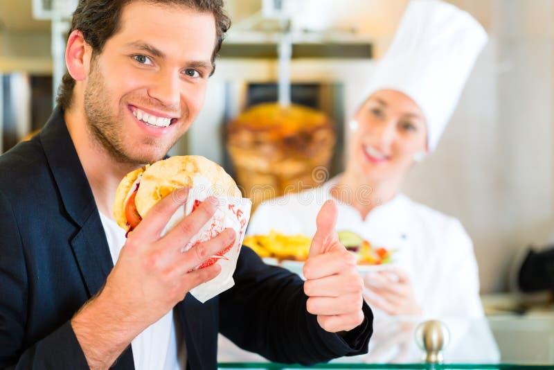 No espeto - cliente e Doner quente com ingredientes frescos foto de stock