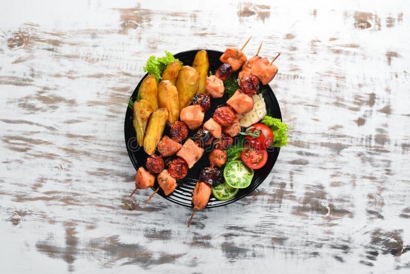 No espeto da galinha com batatas e vegetais em um fundo de madeira branco carne imagem de stock