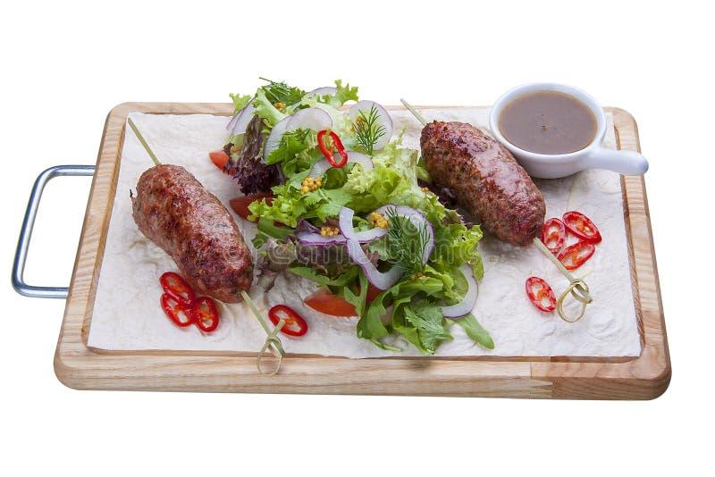 No espeto do cordeiro com salada misturada em uma placa de madeira foto de stock