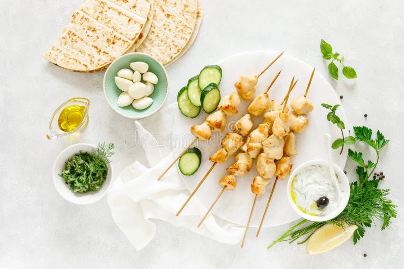 No espeto grelhado da galinha em espetos e no molho grego tradicional do iogurte do tzatziki imagens de stock