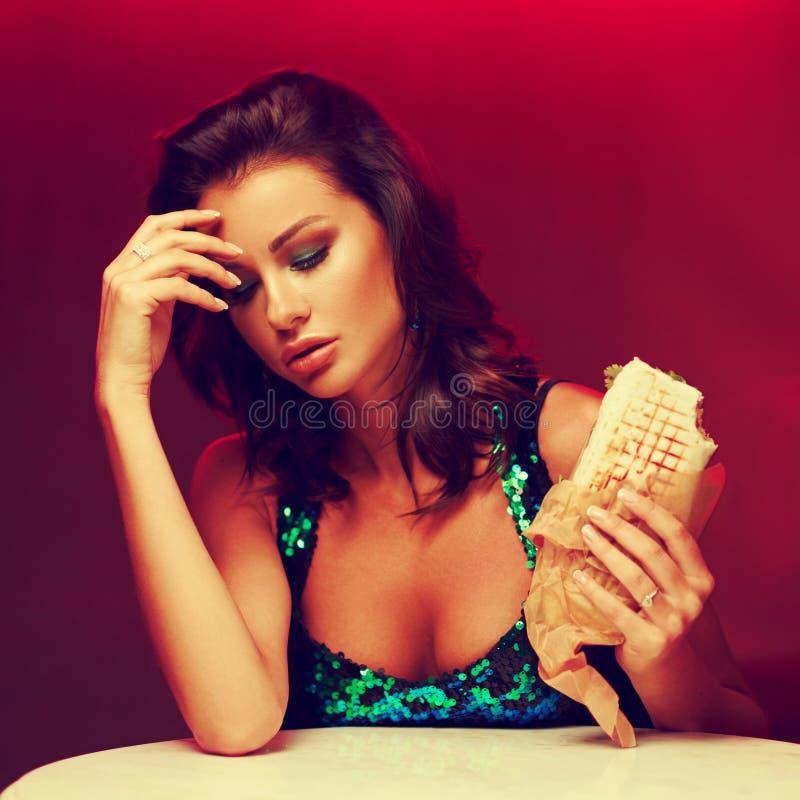 No espeto lindo comer da mulher no clube noturno imagens de stock royalty free