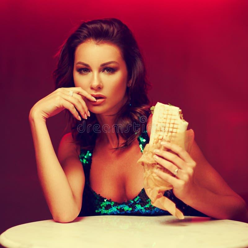 No espeto lindo comer da mulher no clube noturno fotografia de stock