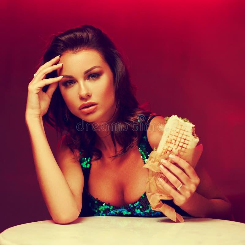 No espeto lindo comer da mulher no clube noturno foto de stock royalty free