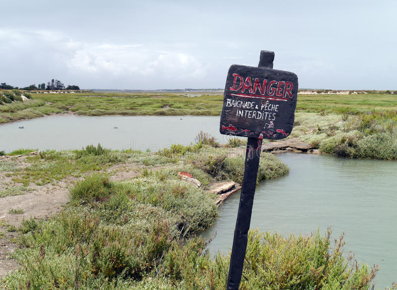 No fishing sign at the salt marshes on Il de Re, France. No fishing sign at the marais on Il de Re, France. Salt marshes in Il de Re. Danger sign royalty free stock image