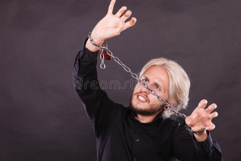 Furious man with chained hands, no freedom. No freedom, social problems concept. Furious man with chained hands, studio shot on dark grunge background royalty free stock photo