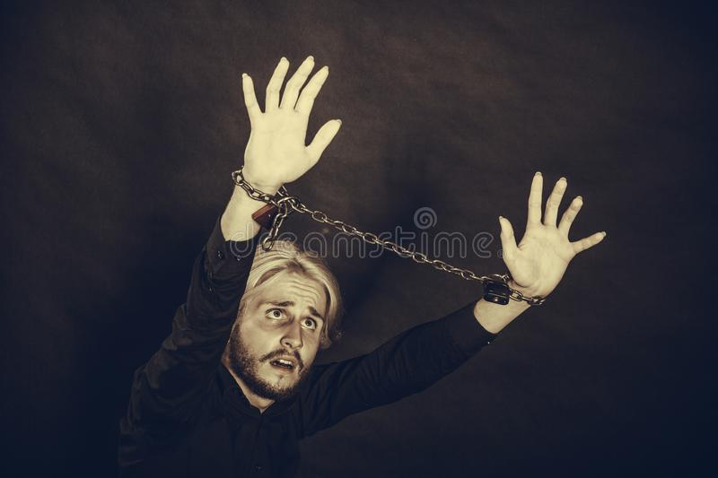 Furious man with chained hands, no freedom. No freedom, social problems concept. Furious man with chained hands, studio shot on dark grunge background stock photography