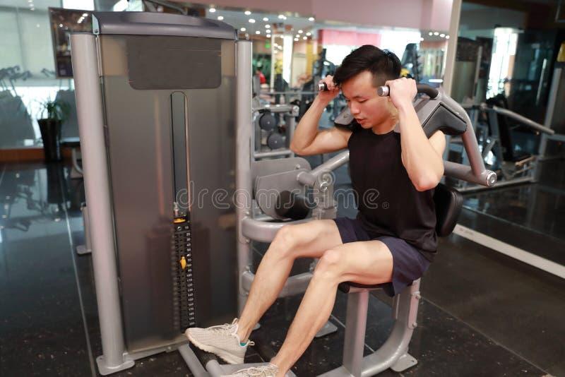 No funcionamento do homem do fitness center O assento magro do homem e o trabalho duro no equipamento de esporte, fazer masculino foto de stock