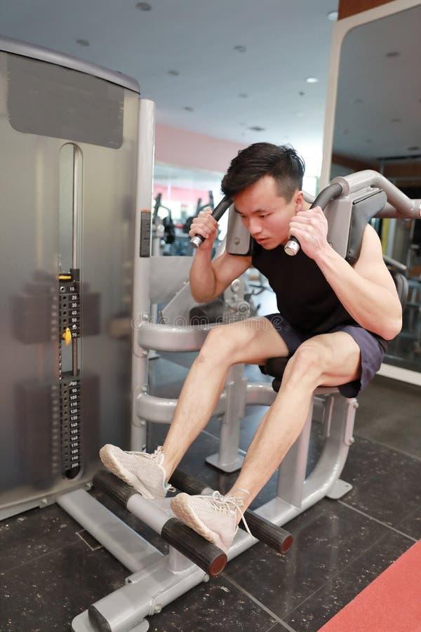 No funcionamento do homem do fitness center O assento magro do homem e o trabalho duro no equipamento de esporte, fazer masculino imagens de stock