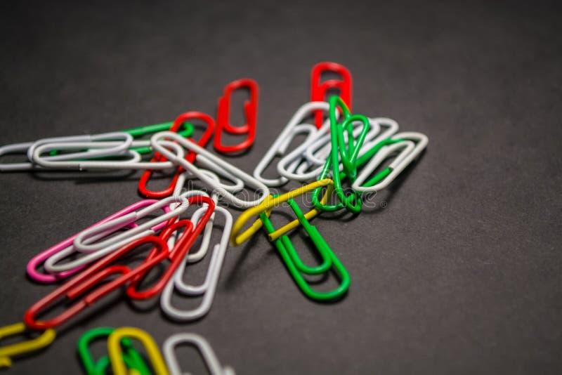 No fundo monofônico preto os clipes de papel multi-coloridos plásticos são mentira Cores brancas, vermelhas, verdes, amarelas esc fotografia de stock