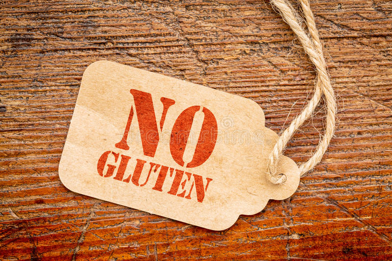 No gluten on paper price tag. No gluten sign - a paper price tag against rustic red painted barn wood stock photography