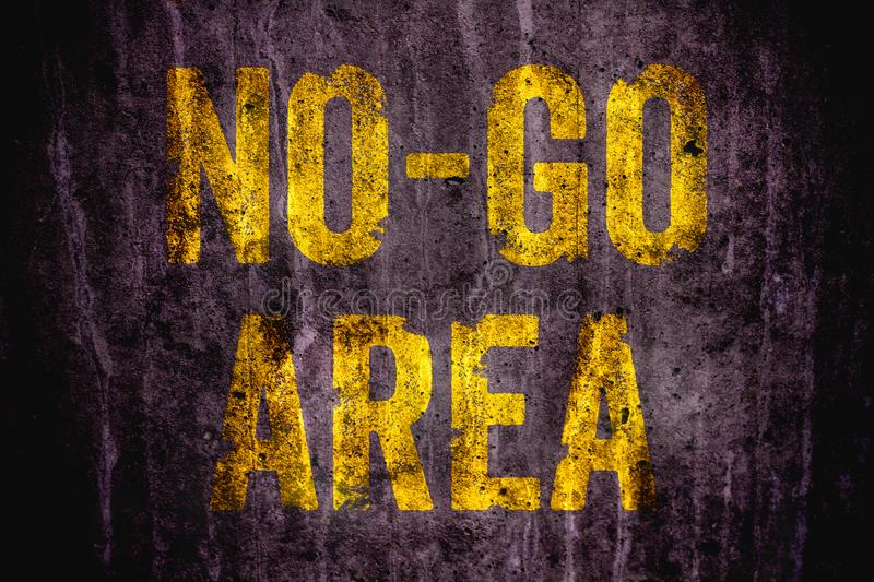 """""""No-Go Area"""" danger warning sign in yellow letters painted over dark grungy concrete wall texture background stock photo"""