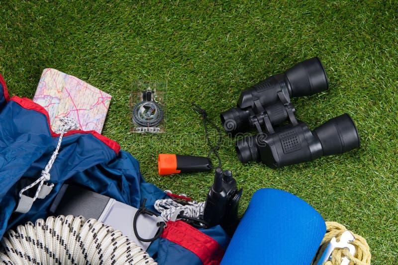 No gramado verde, um grupo de objetos para o turismo, binóculos, lanterna elétrica, compasso, barraca, esteira de acampamento fotos de stock