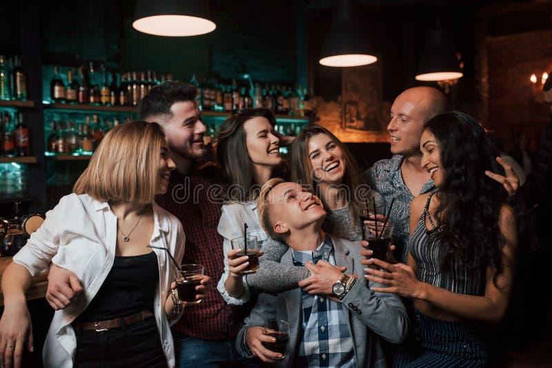 No hay preocupaciones esta noche Los jóvenes hermosos tienen fiesta junto con el alcohol en el club imagen de archivo libre de regalías