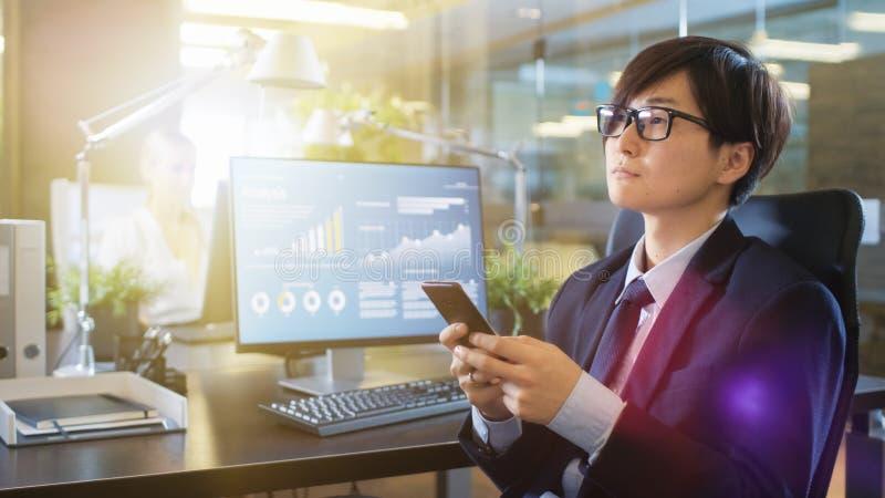 No homem de negócios asiático do leste Uses Smartphone do escritório, travesso de datilografia fotos de stock