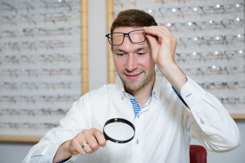 No homem novo da loja do ótico com a lente de aumento que seleciona a leitura nova imagens de stock royalty free