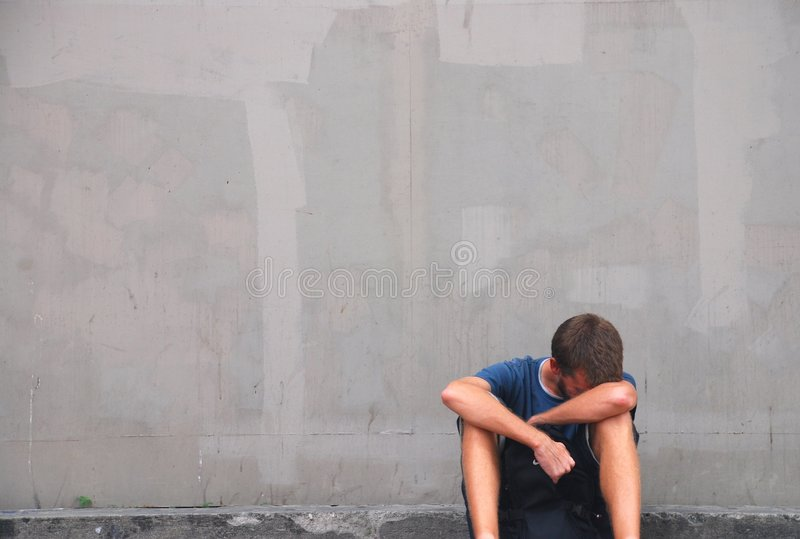 No Hope. A young man, depressed and sitting on a street corner clutching a backpack between his knees stock image