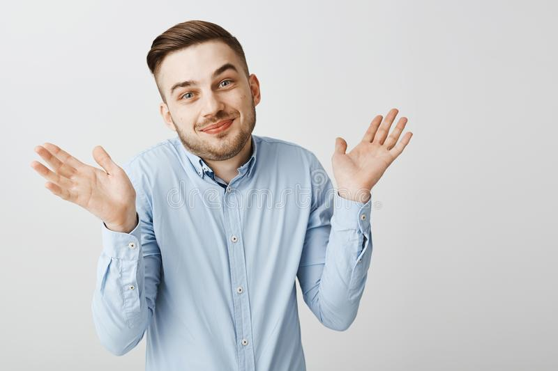 No idea guess yourself. Portrait of happy carefree and careless good-looking male coworker in blue shirt shrugging with royalty free stock photos