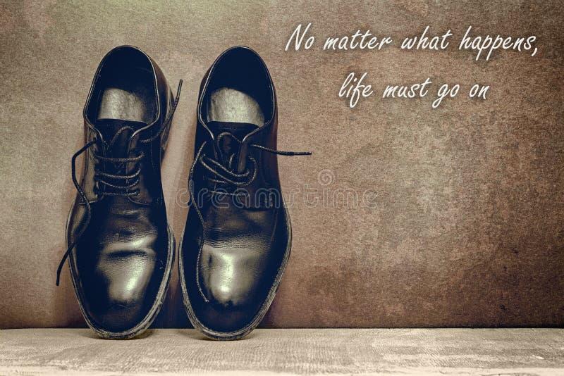 no importa qu? sucede, la vida debe encenderse, tablero y los zapatos de trabajo marrones en piso de madera imagen de archivo libre de regalías