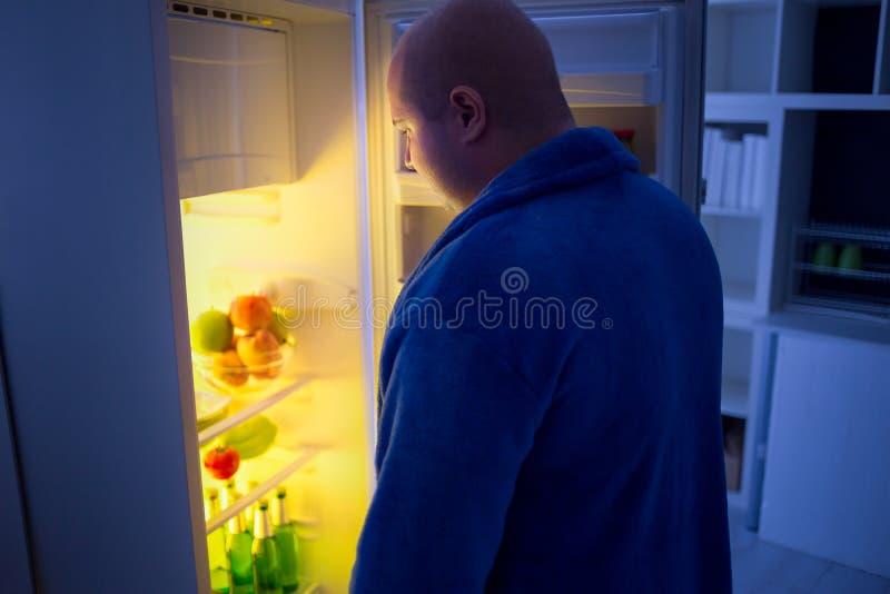 No indivíduo excesso de peso da noite abra o refrigerador imagem de stock