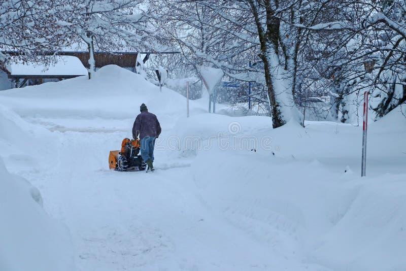 No inverno, um homem cancela a estrada com um ventilador de neve durante a queda de neve pesada foto de stock royalty free