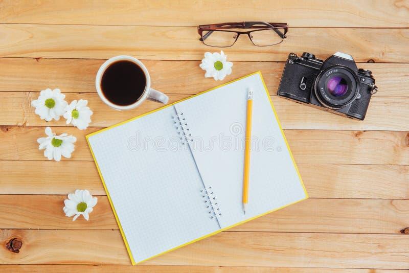 No lápis, no café e em flores de madeira do caderno do fundo fotos de stock royalty free