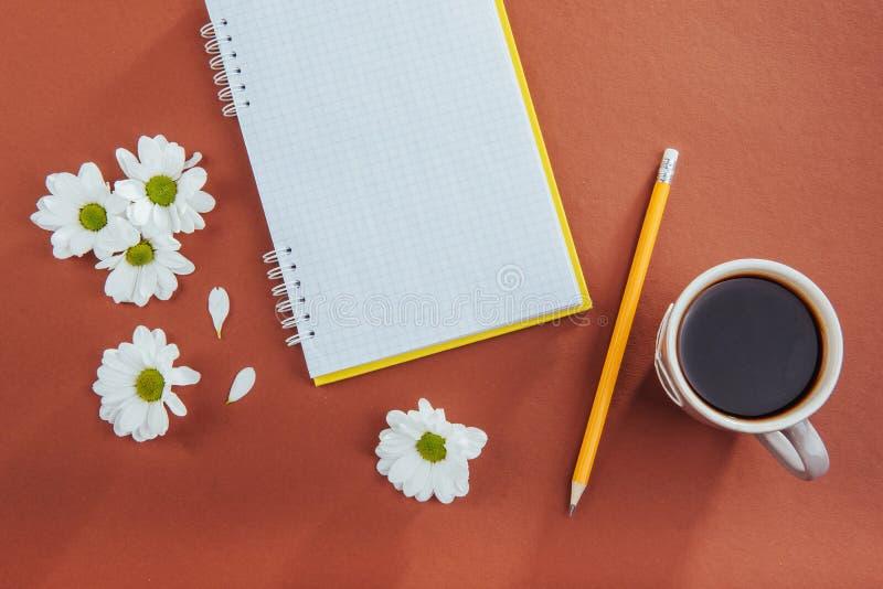 No lápis, no café e em flores de madeira do caderno do fundo imagens de stock royalty free