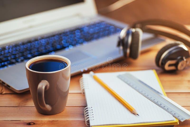 No lápis, na régua e no café de madeira do caderno do fundo Portátil no fundo branco e em fones de ouvido pretos foto de stock