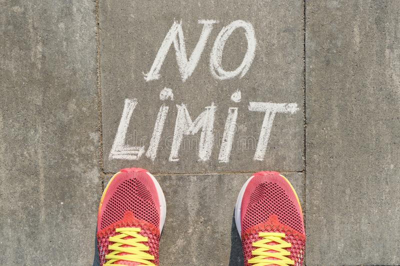 No limit text on gray sidewalk with woman legs in sneakers, top view royalty free stock photo