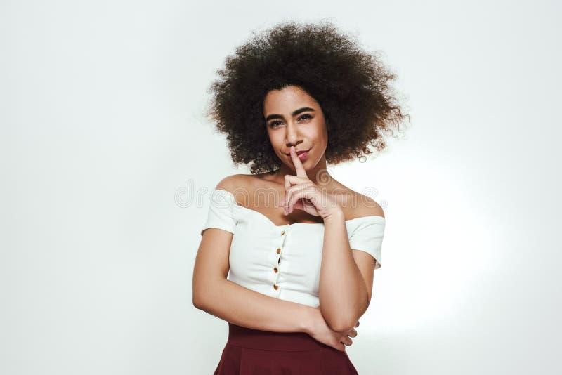No mówi ktokolwiek Piękna i śliczna afro amerykańska kobieta pokazuje tss i ono uśmiecha się przy kamerą podczas gdy stojący prze fotografia royalty free