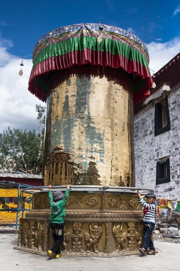 Two Tibetan boy rotating building sized prayer wheel , Tibet royalty free stock photography