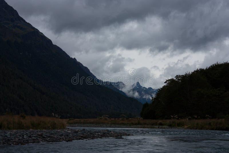 No meio de um rio que olha uma montanha em Fiordland na ilha sul em Nova Zelândia fotografia de stock