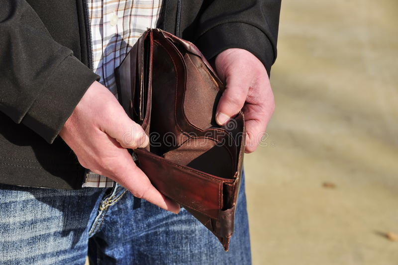 No money. Man is lokking for money in empty wallet stock photo