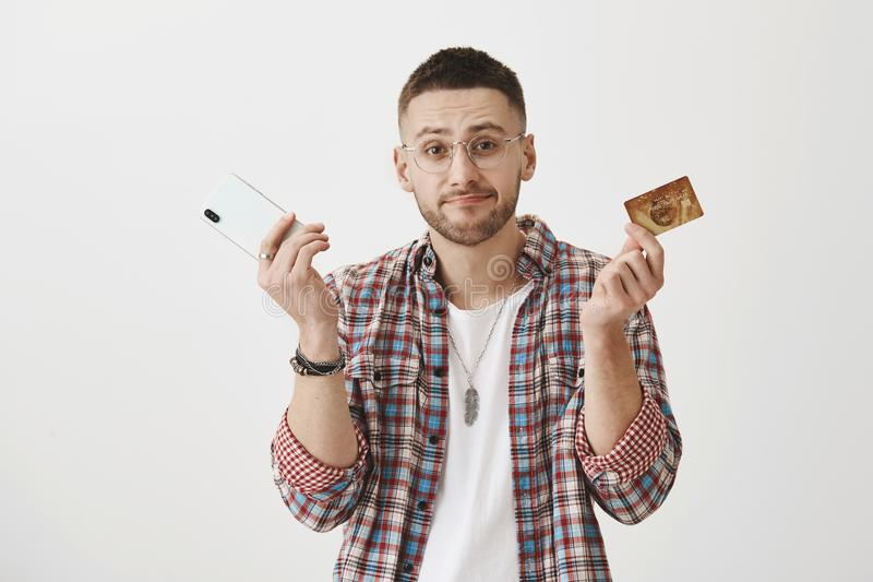 No money no smartphone. Portrait of gloomy displeased handsome employee, shrugging and lifting eyebrows in despair while. Showing credit card and phone, feeling stock images