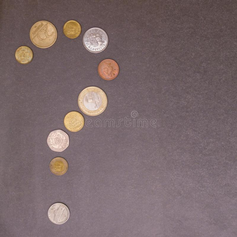 No money. The question mark consists of small coins. Inconsistency of income and expenses, debts, taxes, lack of cash. Gray background royalty free stock photos