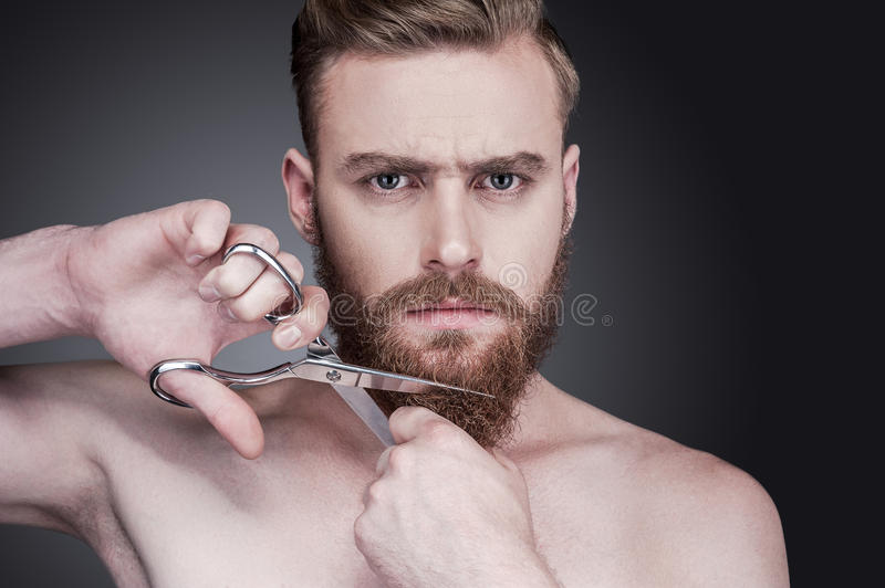No more beard. Portrait of handsome young shirtless man cutting his beard with scissors and looking at camera while standing against grey background