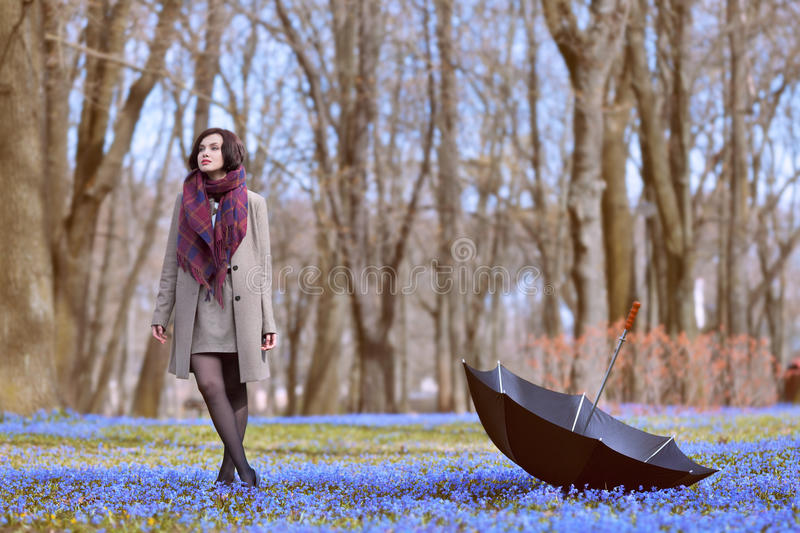 No more rain. Beautiful woman walking in the park at spring time stock image