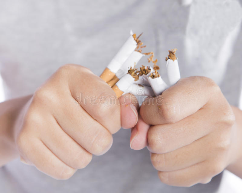 No more smoking. Closeup of girl in grey t-shirt breaking cigarettes for health reason, broken cigarette in hand stock image