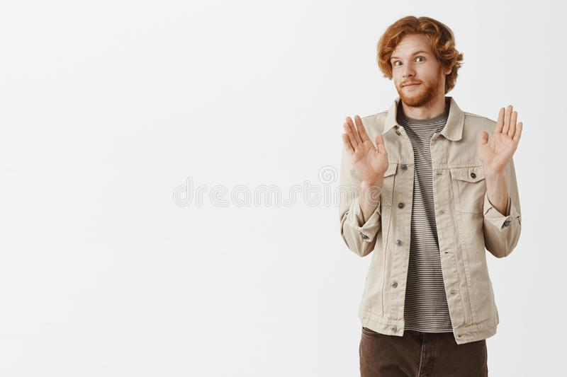 No offence sorry pal. Portrait of intense redhead male with beard feeling awkward smiling tight from discomfort raising. Palms in surrender and turning away stock photography