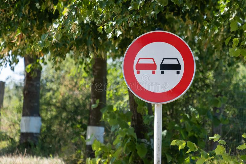 No Overtaking Road Sign Green Background. No Overtaking road sign on green lushy background stock photo