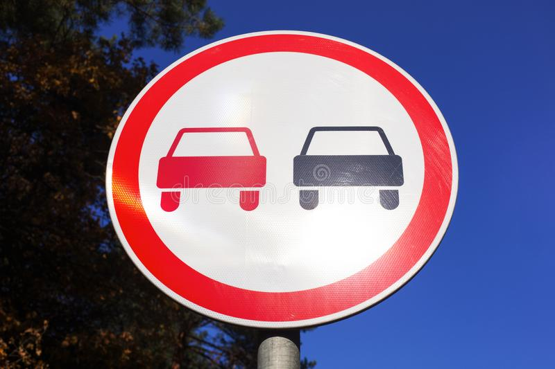 No Overtaking road sign. Against blue sky and tree stock photography
