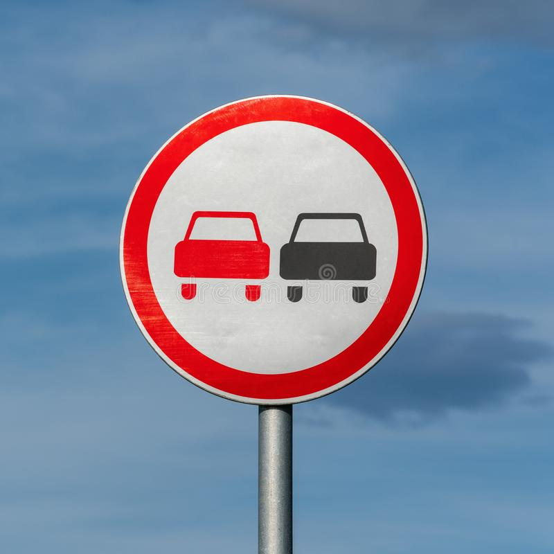No overtaking road traffic sign on background of blue sky with clouds. Warning and information road traffic street sign, complianc. E with rules. Copy space stock images