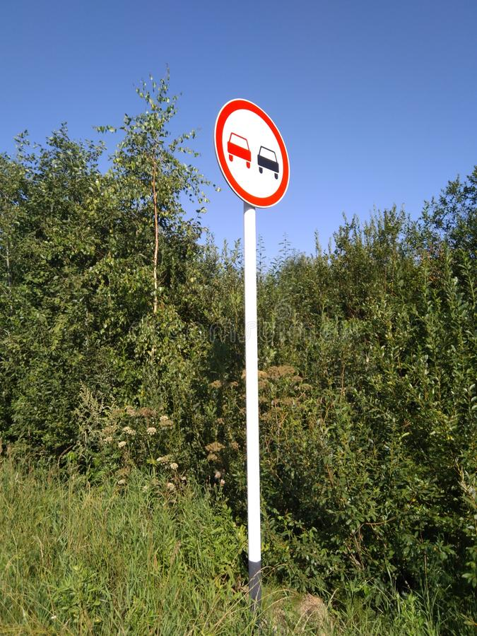 `No overtaking` Roadsign On a White Pole. A `no overtaking` roadsign with a white pole in Russia royalty free stock photography