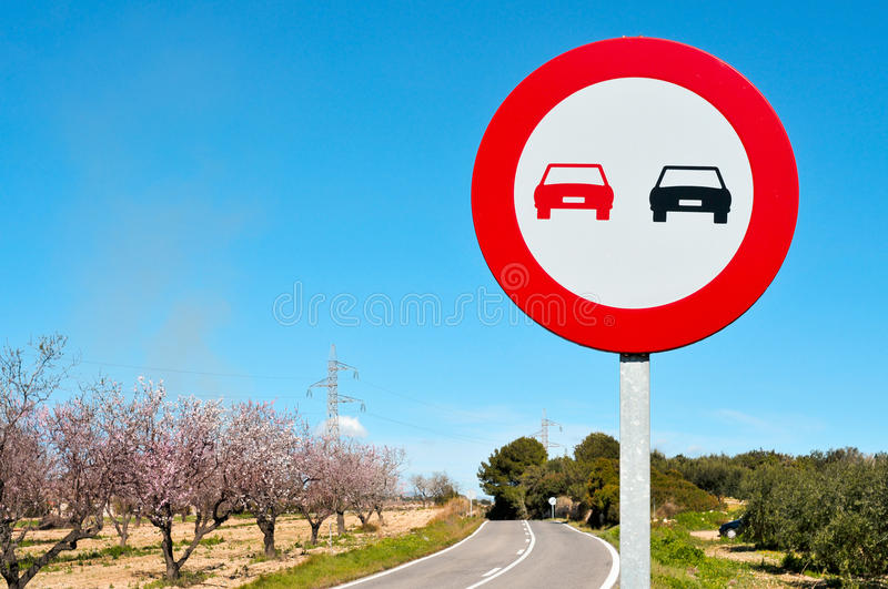 No overtaking sign in a secondary road. With almond trees in full bloom stock photo