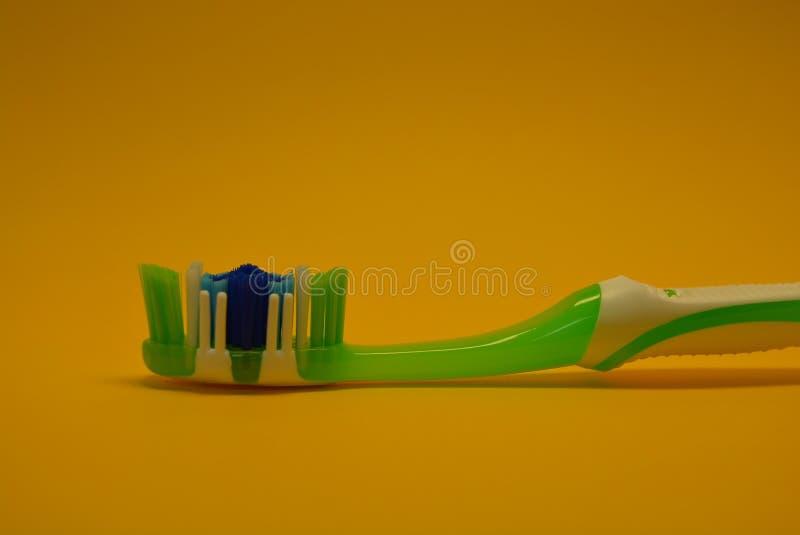 No papel do amarelo um fundo é encontrado e colocou uma escova de dentes nova para os dentes de limpeza esverdeia, branco e azul fotografia de stock