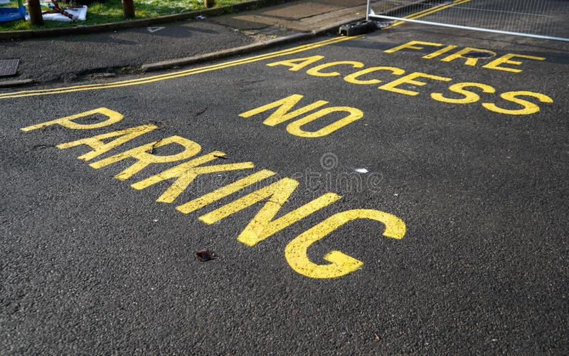 No parking, Fire access text sign with double yellow line on asphalt road. royalty free stock photo