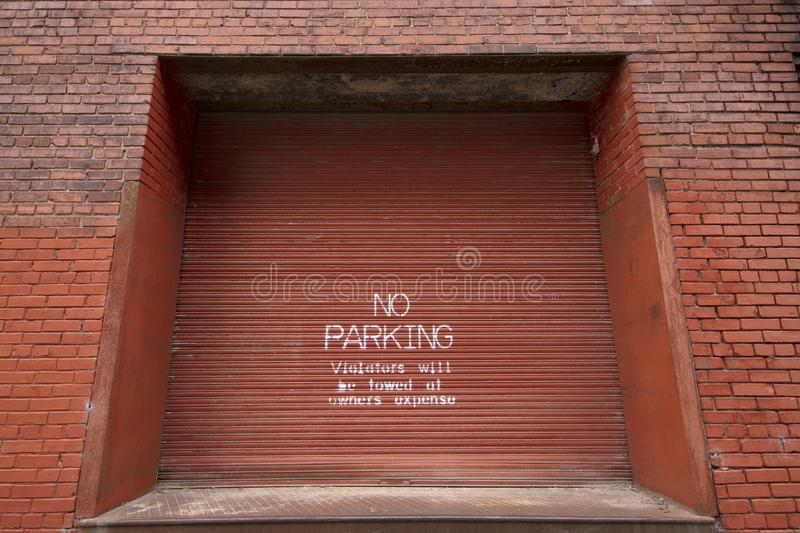 A no parking painted on a warehouse door stock photography